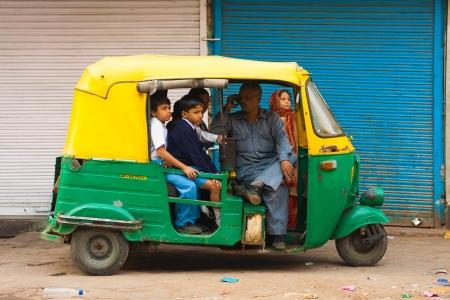 transporte escolar: DELHI, INDIA - 27 de octubre de 2009: Los niños esperan a ser transportados a la escuela en un auto rickshaw privado el 27 de octubre de 2009 en Delhi, India. Las escuelas no ofrecen transporte escolar compartido en la India. Editorial