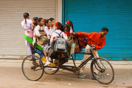 DELHI, INDIA - OCTOBER 27, 2009: Young girls ride a crammed private cycle rickshaw to school on October 27, 2009 in Delhi, India. Schools do not provide shared bus transportation in India.