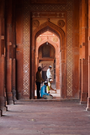 fatehpur: FATEPHUR SIKRI, INDIA - NOVEMBER 18, 2009: Muslims pray inside the doorway of the fort mosque, a famous tourist attraction, for afternoon prayers on November 18, 2009 in Fatephur Sikir, India Editorial