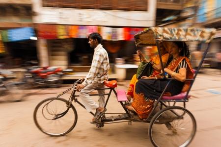 MATHURA, INDIA - NOVEMBER 13, 2009: Two Indian women laugh riding a cycle rickshaw, a popular form of taxi, through a busy bazaar on November 13, 2009 in Mathura, India