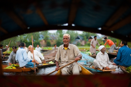 SRINAGAR, INDIA - JULY 11, 2009: A taxi boatman paddles through the sellers of the floating market, a major tourist attraction on Dal Lake on July 11, 2009 in Srinagar, India