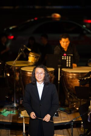 accepts: SEOUL, KOREA - SEPTEMBER 23, 2009: An unidentified conductor of a symphany orchestra accepts applause in the spotlight at a free summer night concert series on September 23, 2009 in Seoul, Korea