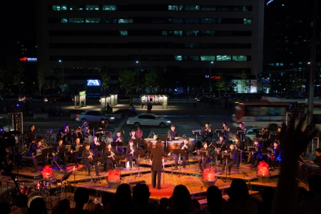 SEOUL, KOREA - SEPTEMBER 23, 2009: A full symphany orchestra plays music on a sidewalk near downtown traffic at a free summer night concert series on September 23, 2009 in Seoul, Korea 新聞圖片