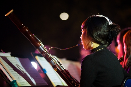 SEOUL, KOREA - SEPTEMBER 23, 2009: An unidentified female member of a symphany orchestra plays a bassoon at a free summer night concert series on September 23, 2009 in Seoul, Korea