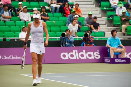 tennis stadium: SEOUL, KOREA - SEPTEMBER 23, 2009: Russian professional womens tennis player, Maria Kirilenko walks on the baseline during a lull at the Hansol Korea Open on September 23, 2009 in Seoul, Korea