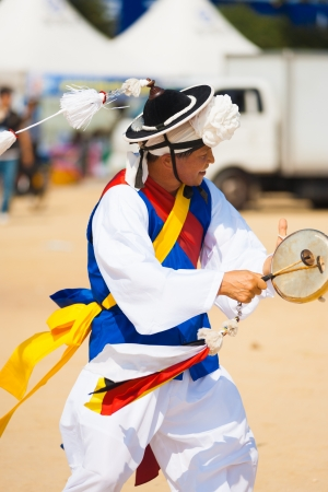 SEOUL, KOREA - SEPTEMBER 18, 2009: An unidentified Korean man dressed in traditional clothes dances and drums while spinning his hat tassle at a local festival on September 18, 2009 in Seoul, Korea