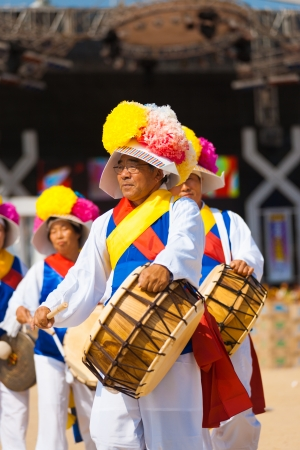 SEOUL, KOREA - SEPTEMBER 18, 2009: An older unidentified man plays a traditional Korean drum in colorful clothes at a local outdoor festival on September 18, 2009 in Seoul, Korea