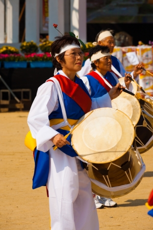 SEOUL, KOREA - SEPTEMBER 18, 2009: An unidentified Korean woman dressed in festive traditional clothes beats her janggu drums at a local outdoor festival on September 18, 2009 in Seoul, Korea