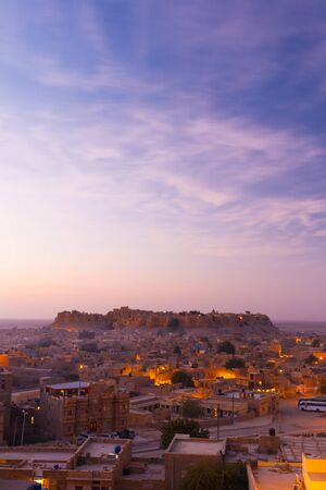 A massive fort is seen surrounded by neighborhood houses on a beautiful clear morning in Jaisalmer, Rajasthan, India.  Vertical copy space. photo