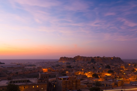 Jaisalmer fort wakes and its surround neighborhood houses wake up to a beautiful pink cloud sunrise in Rajasthan, India photo
