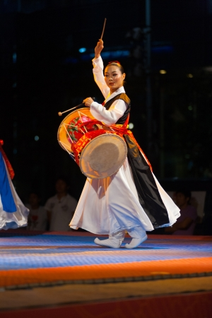 SEOUL, KOREA - SEPTEMBER 17, 2009: An unidentified traditionally dressed Korean woman plays the janggu drums at a free summer show near city hall on September 17, 2009 in Seoul, Korea. Raised Arm