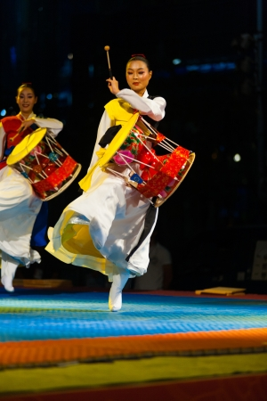 SEOUL, KOREA - SEPTEMBER 17, 2009: An unidentified Korean woman in traditional hanbok jumps and plays the janggu drums at a free summer show near city hall on September 17, 2009 in Seoul, Korea