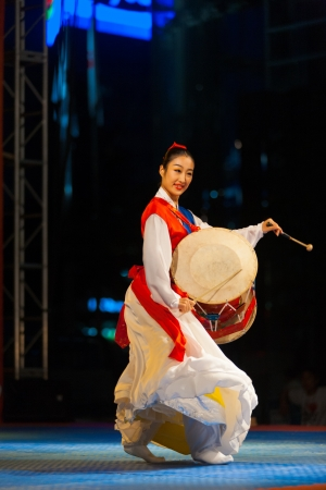 SEOUL, KOREA - SEPTEMBER 17, 2009: An unidentified Korean woman dances, plays traditional janggu drums at an open-air summer performance near city hall on September 17, 2009 in Seoul, Korea. Profile