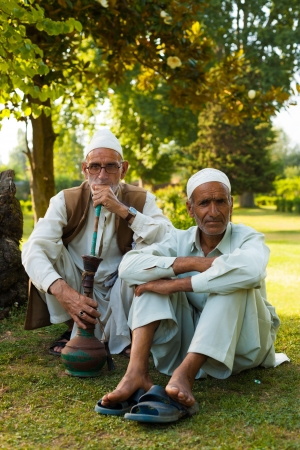 SRINAGAR, INDIA - JULY 9, 2009: Unidentified Kashmiri muslim men sit in the beautiful nature of Kashmir smoking a shisha in the outdoors on July 9, 2009 in Srinagar, India