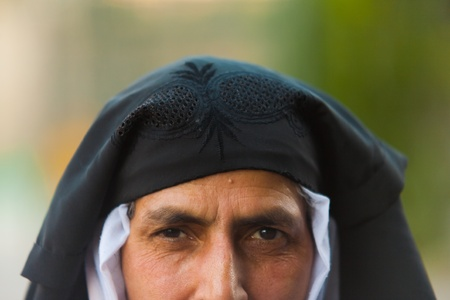 SRINAGAR, INDIA - JULY 11, 2009: An unidentified Kashmiri muslim woman pulls back her veil exposing her face on July 11, 2009 in Srinagar, India. Many Kashmiris practice a less strict form of Islam