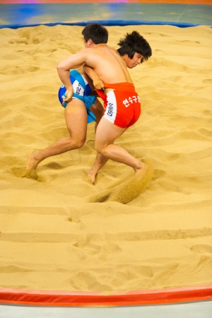 bout: JEUNGPYEONG, KOREA - SEPTEMBER 18, 2009: Two unidentified ssireum wrestlers, the Korean national sport similar to sumo, attempt to throw each other down on September 18, 2009 in Jeungpyeong, Korea