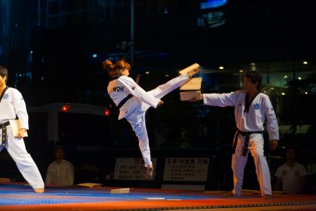 SEOUL, KOREA - SEPTEMBER 17, 2009: An unidentified taekwondo girl in mid-air jump kicks and breaks a wood board at a free open-air summer show near city hall on September 17, 2009 in Seoul, Korea Editoriali