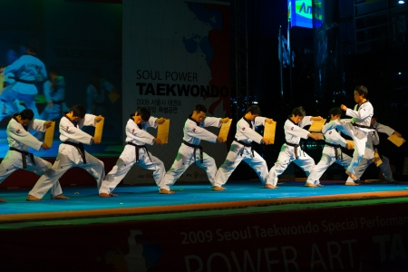 SEOUL, KOREA - SEPTEMBER 17, 2009: An unidentified taekwondo expert jump kicks and breaks a series of wood boards at a free open-air summer show near city hall on September 17, 2009 in Seoul, Korea