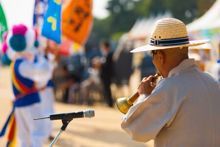 SEOUL, KOREA - SEPTEMBER 18, 2009: An unidentified Korean man plays a traditional wind instrument, taepyeongso for a dance group at a local outdoor festival on September 18, 2009 in Seoul, Korea