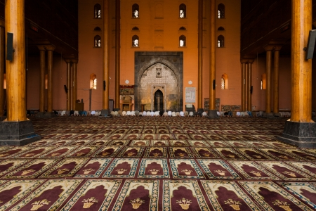 SRINAGAR, INDIA - JULY 11, 2009: A row of muslims pray in the oversized prayer hall in the Main Mosque, Jama Masjid, for evening prayers in Kashmir on July 11, 2009 in Srinagar, India. H