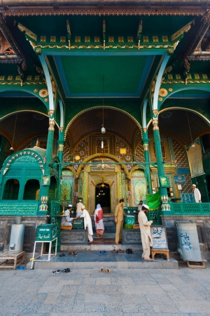 uniquely: SRINAGAR, INDIA - JULY 22, 2009: Unidentified muslims enter a uniquely wooden mosque, Shah E Hamdan, a major tourist attraction, for evening prayers in Kashmir on July 22, 2009 in Srinagar, India Editorial