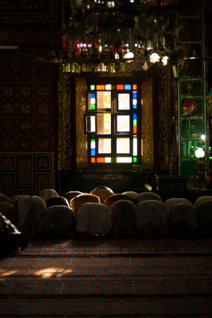 kashmir: SRINAGAR, INDIA - JULY 22, 2009: Unidentified muslim men bow inside the wooden mosque, Shah E Hamdan, a major tourist attraction, for evening prayers in Kashmir on July 22, 2009 in Srinagar, India V