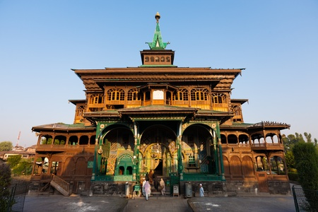 kashmir: SRINAGAR, INDIA - JULY 15, 2009: Unidentified muslim women enter the uniquely wooden Shah E Hamdan mosque, a major Kashmir tourist attraction, for morning prayers on July 15, 2009 in Srinagar, India Editorial