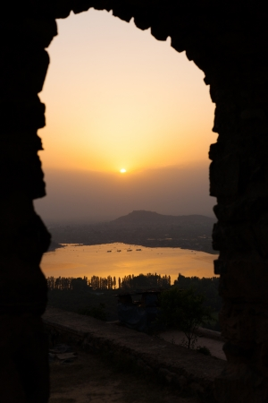 A lovely sunset is seen through a framed silhouette gateway over Dal Lake and the fort in the distance in Srinagar, Kashmir, India photo