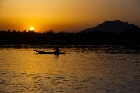 kashmir: The silhouette of a boat glides along the surface of Dal Lake during sunset with Srinagar Fort in the background in Kashmir, India