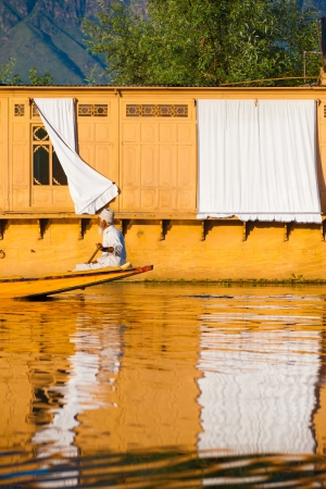 kashmir: SRINAGAR, INDIA - JULY 7, 2009: An unidentified muslim boatman rows past a house boat hotel, a major Kashmir tourist attraction, on Dal Lake on July 7, 2009 in Srinagar, India