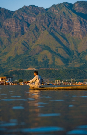 SRINAGAR, INDIA - JULY 10, 2009: An unidentified Kashmiri Muslim man rows his boat on the tourist destination of Dal Lake, surrounded by mountains in Kashmir on July 10, 2009 in Srinagar, India