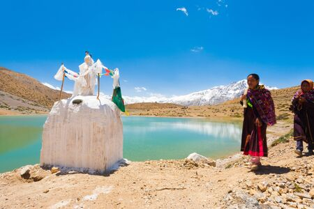 DHANKAR, INDIA - JUNE 7, 2009: Unidentified Buddhist pilgrims walk on pilgrimage past a stupa around a pristine alpine lake in the Himalayas in the Spiti Valley on June 7, 2009 in Dhankar, India Editorial