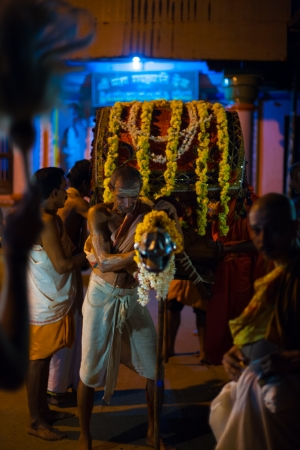 GOKARNA, INDIA - MARCH 26, 2009: Unidentified Indian brahmins pull a highly decorated palanquin at night during a monthly full moon hindu ceremony on March 26, 2009 in Gokarna, India 新聞圖片