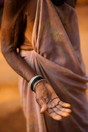 GOKARNA, INDIA - MARCH 9, 2009: A poor old Indian senior woman extends her hand and palm to ask for money and change on March 9, 2009 in Gokarna, India