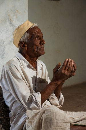 BIJAPUR, INDIA - FEBRUARY 19, 2009: An unidentified Indian male begs with his hands out at the entrance of a mosque on February 19, 2009 in Bijapur, India. Poverty is a major social issue in India