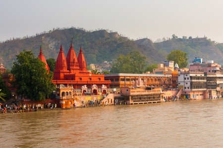 HARIDWAR, INDIA - MAY 21, 2009: Unidentified Hindus gather at a pilgrimage spot near a red temple to bathe in the Ganges River for purification on May 21, 2009 in Hardiwar, India
