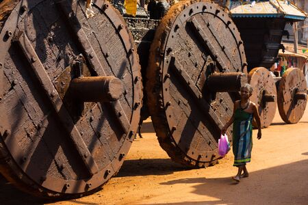 oversized: GOKARNA, INDIA - MARCH 3, 2009: Unidentified Indian woman walks by enormous wooden wheels of the big ratha chariot, a vehicle used in Gokarna for hindu festivals, on March 3, 2009 in Gokarna, India