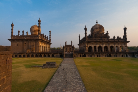 extends: A footpath extends to the rear of the historic landmark mausoleum, the Ibrahim Roza, a famous landmark in Bijapur, India and purported inspiration for the Taj Mahal of Agra