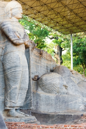 monolithic: A newly constructed roof covers and protects the monolithic standing and reclining Buddha statues, the Gal Viharaya, carved from a single piece of striated granite in Polonnaruwa, the ancient kingdom capitol of Sri Lanka Stock Photo