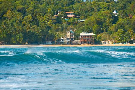 The rear of a superb surfable wave rolls toward the beach of Unawatuna, a notable surf spot in Sri Lanka photo