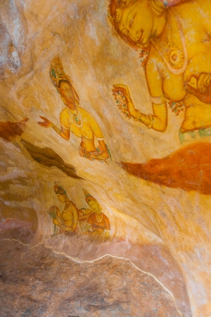 The ancient hand painted cave frescoes of women inside Sigiriya rock, a former fortress and monastery in Sri Lanka. Vertical