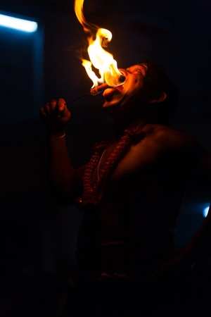 KANDY, SRI LANKA - MAY 6, 2008: An unidentified shirtless man tastes a flaming stick during a night street fire eating show at a local festival on May 6, 2008 in Kandy, Sri Lanka