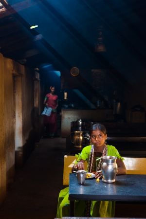 lightbeam: GOKARNA, INDIA - MARCH 29, 2009: An Indian woman eats a quick meal with her right hand at a typical atmospheric dhaba, an Indian fast food restaurant, on March 29, 2009 in Gokarna, India