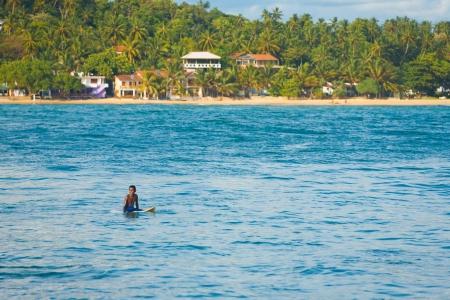 notable: UNAWATUNA, SRI LANKA - MAY 21, 2008: An unidentified local Sri Lankan surfer sits on his board in a calm ocean at a notable surfing destination on May 21, 2008 in Unawatuna, Sri Lanka