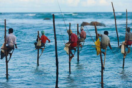 lanka: UNAWATUNA, SRI LANKA - MAY 22, 2008: Unidentified Sri Lankan stilt fishermen catch small fish in this unique traditional method sitting above the water on May 22, 2008 in Unawatuna, Sri Lanka