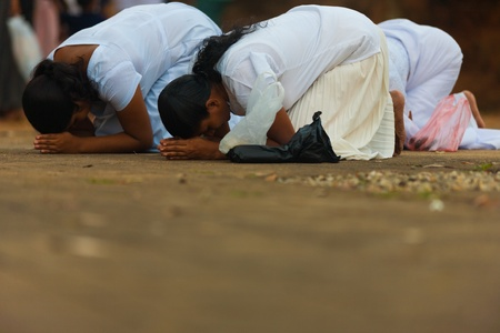 UNAWATUNA, SRI LANKA - MAY 19, 2008: Sinhalese buddhist women at a local temple bow low in prayer on Vesak Full Moon Poya Day, a major national holiday on May 19, 2008 in Unawatuna, Sri Lanka