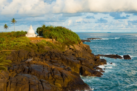 A white stupa stands atop a beautiful headland surrounded by ocean in Unawatuna, Sri Lanka