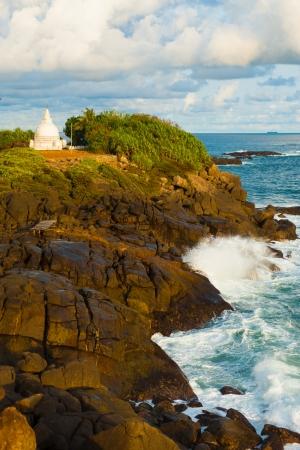 headland: Landscape of a wave crashing over the rocks of a headland containing a white dagoba or stupa in Unawatuna, Sri Lanka