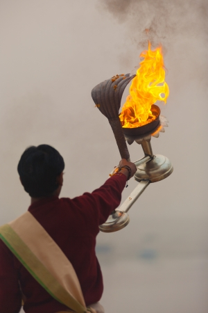VARANASI, INDIA - FEBRUARY 1, 2008: An unidentified hindu brahmin priest extends a naga snake fire lantern to lead a pooja prayer on the Ganges river ghats on February 1, 2008 in Varanasi, India