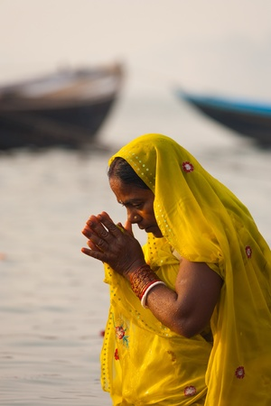 ganges: VARANASI, INDIA - JANUARY 29, 2008: A devout hindu woman bows, prays and bathes with hands clasped, an important cultural tradition, in the holy Ganges river on January 29, 2008 in Varanasi, India